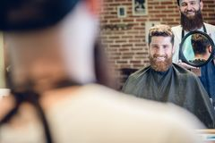 Young man smiling while looking at his new trendy haircut in the. Over the shoulder view of a handsome young men smiling while looking at his new trendy haircut stock photography