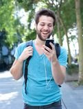 Young man smiling and looking at mobile phone. Portrait of a young man smiling and looking at mobile phone Royalty Free Stock Photos