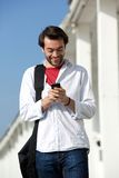 Young man smiling and looking at mobile phone Stock Photography