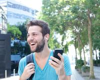 Young man smiling with mobile phone and earphones. Close up portrait of a handsome young man smiling with mobile phone and earphones Royalty Free Stock Photo