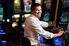 Young man smiling next to the slot machine. Young man standing next to the slot machine smiling royalty free stock photos