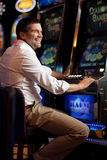 Young man smiling next to the slot machine Royalty Free Stock Images