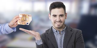 Man accepting money. Young man smiling with outstretched hand receiving money Royalty Free Stock Photos
