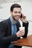Young man smiling with phone and coffee Stock Image