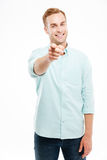 Young man smiling and pointing at camera over white background Stock Photo
