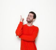 Young man smiling and pointing finger Stock Photos