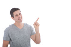 Young man smiling while pointing up to his left Stock Images
