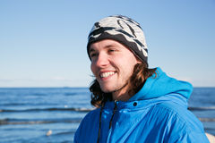 Young happy man portrait on the beach. Cold sunny day Royalty Free Stock Photography