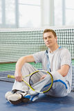 Young man smiling and posing with tennis racket indoor Royalty Free Stock Images