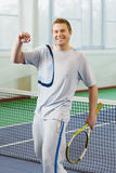 Young man smiling and posing with tennis racket indoor Stock Photos