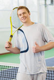 Young man smiling and posing with tennis racket indoor Stock Image
