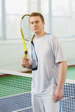 Young man smiling and posing with tennis racket indoor Stock Photo