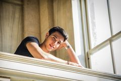 Young Man Smiling, Resting with Head on Staircase Royalty Free Stock Image