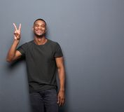 Young man smiling showing hand peace sign. Portrait of a young man smiling showing hand peace sign royalty free stock photos