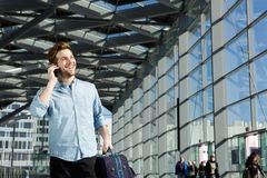 Young man smiling at station with bag and mobile phone Stock Photo