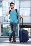 Young man smiling with suitcase at airport Stock Photography