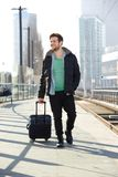 Young man smiling with suitcase on train station platform Royalty Free Stock Images