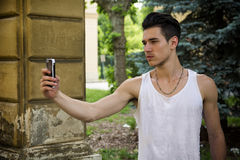 Young man smiling and taking photo with cell phone Royalty Free Stock Photo