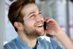 Young man smiling and talking on cell phone Royalty Free Stock Images