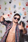 Young man smiling with thumbs up  on a funny background. Young man smiling with thumbs up  in sunglasses  on a funny hands background Royalty Free Stock Photography