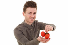 Young man smiling with tomatoes Royalty Free Stock Image