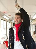 Young man smiling traveling by public transport Royalty Free Stock Images