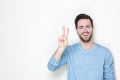 Young man smiling with victory sign Royalty Free Stock Photography