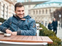 Young man smiling and waiting for drink in the cafes . Happy laughing guy royalty free stock images