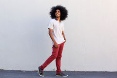 Young man smiling and walking by white wall Stock Photography