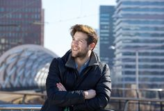 Young man smiling with winter jacket in the city. Close up portrait of a young man smiling with winter jacket in the city Royalty Free Stock Images