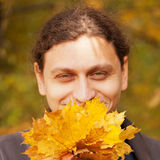 Young  man smiling with yellow leaves Stock Images