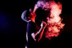 Young man smoke. Vaping man holding a mod. A cloud of vapor. Black background. Vaping an electronic cigarette with a lot of smoke. Vape concept stock image