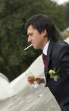 Young man smokes a cigarette. And drinks wine Royalty Free Stock Photography