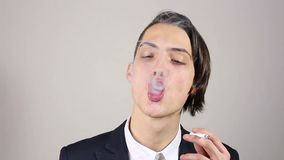 A young man smokes a cigarette on a gray background stock footage