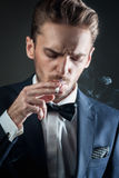 Young man smokes a cigarette. Portrait of a young sexy man smoking a cigarette, nice smoke. A man dressed in a classic suit, white shirt, bow tie. Isolated shot Stock Photos
