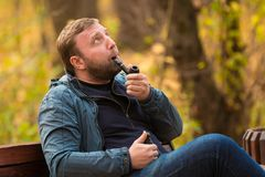 Young man smokes tobacco pipe in park. In autumn time Stock Photo