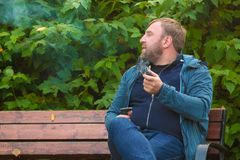 Young man smokes tobacco pipe in park. In autumn time Royalty Free Stock Photography