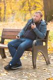 Young man smokes tobacco pipe in park. In autumn time Royalty Free Stock Photos