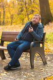 Young man smokes tobacco pipe in park. In autumn time Stock Photography