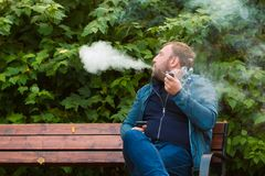 Young man smokes tobacco pipe in park. In autumn time Stock Image
