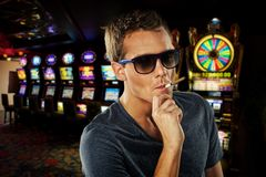 Young man smoking in casino Stock Image