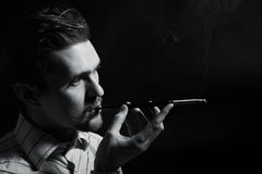 Young man smoking a cigarette Royalty Free Stock Image
