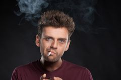 Young man smoking cigarette on black background. Stock Image