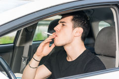 Young Man smoking cigarette while Driving Royalty Free Stock Photo