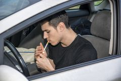Young Man smoking cigarette while Driving Stock Images