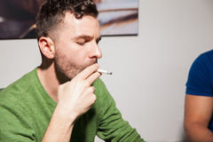 Young man smoking a cigarette Stock Photography