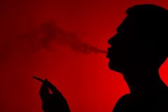 Young man smoking cigarette on red. Stock Image