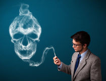 Young man smoking dangerous cigarette with toxic skull smoke Royalty Free Stock Photo