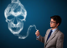 Young man smoking dangerous cigarette with toxic skull smoke Stock Photography