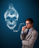 Young man smoking dangerous cigarette with toxic skull smoke Stock Photos